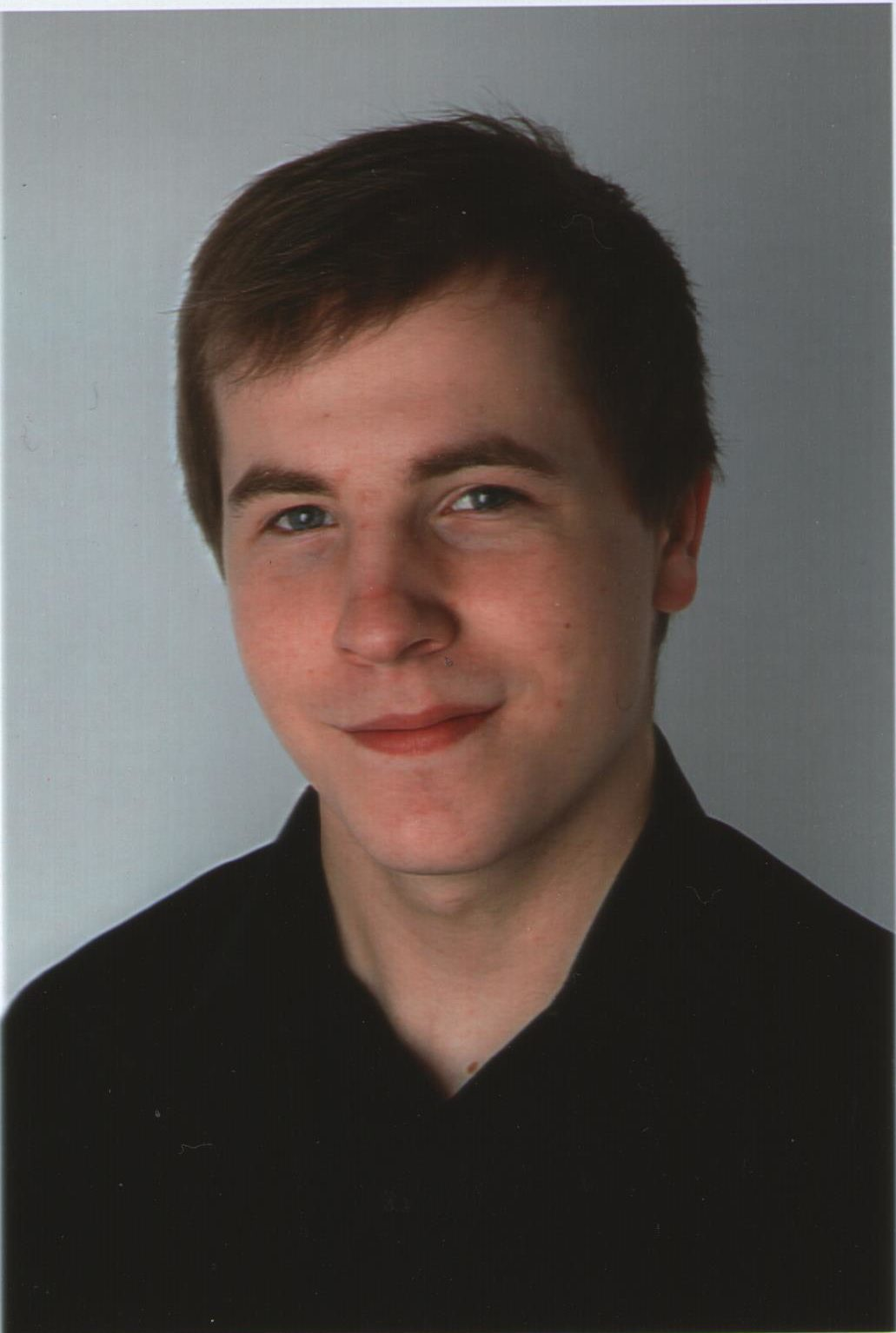 Portraitaufnahme eines Mannes in einem schwarze Hemd.